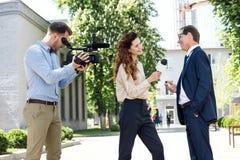 摄影师和女性新闻广播员采访的商人 库存图片