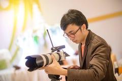 摄影师和录影制造商人拿着在他的手上的DSLR照相机对做英尺长度 免版税图库摄影