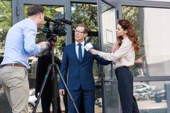摄影师和新闻记者有恼怒的商人的 免版税库存照片