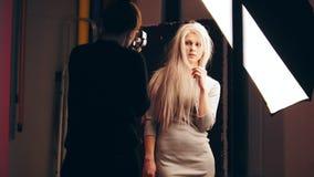 摄影师和有吸引力的白肤金发的女性模型在照片演播室-摄影师` s工作 影视素材
