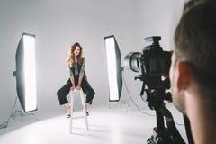 摄影师和模型在演播室 免版税库存照片