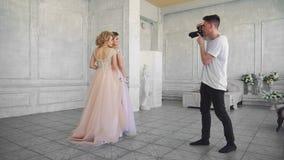 摄影师在一个白色内部演播室为两个美丽的女孩照相 股票视频