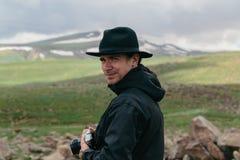 摄影师在亚美尼亚山的手上拿着一台照相机 免版税库存照片