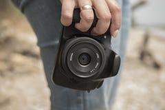 摄影师在他的手上拿着一台照相机 库存照片