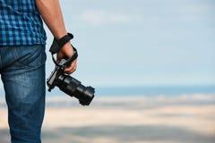 摄影师在他的手上的拿着一台照片数字照相机 库存照片