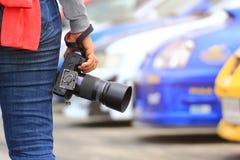 摄影师在他的手上的拿着DSLR照相机有身分的在汽车停车场 免版税库存图片