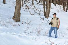 摄影师在冬天森林里 免版税库存照片