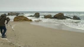 摄影师在岩石和风雨如磐的海附近调整在三脚架的照相机在沙子海滩 股票录像