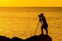 摄影师在日落现出轮廓 库存图片