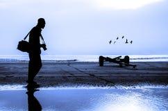 摄影师在海滩附近的剪影射击 免版税库存照片