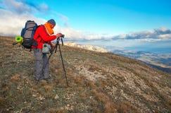 摄影师在秋天拍照片在山顶部 免版税库存照片