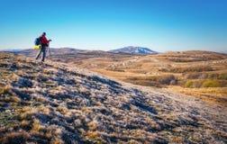 摄影师在秋天拍照片在山顶部 库存图片