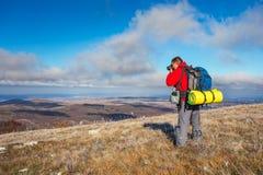 摄影师在秋天拍照片在山顶部 免版税库存图片