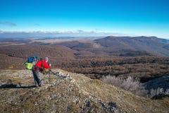 摄影师在秋天拍照片在山顶部 库存照片