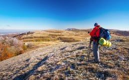 摄影师在秋天拍照片在山顶部 免版税图库摄影