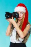 摄影师女孩在圣诞老人帽子射击图象 免版税库存图片