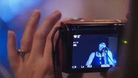 摄影师妇女拿着小配件的` s手在摇滚乐音乐会期间 免版税图库摄影