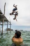 摄影师射击2个Bajau孩子翻筋斗从他们的房子之外入海 免版税图库摄影
