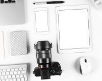 摄影师工作场所顶视图:键盘、片剂、照相机和智能手机在白色书桌背景 免版税库存图片