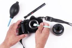 摄影师手照相机清洁传感器通过使用传感器拖把的 免版税库存图片