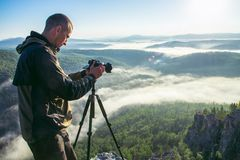 摄影师拍与照相机的照片在落矶山脉峰顶的三脚架 美好的有薄雾的日出和谷视图 库存照片