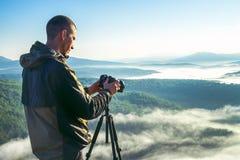 摄影师拍与照相机的照片在落矶山脉峰顶的三脚架 美好的有薄雾的日出和谷视图 免版税库存图片