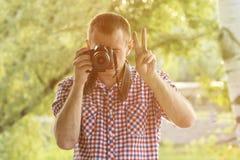 摄影师拍照片以绿叶为背景 正面图 胜利手 免版税图库摄影
