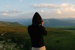 摄影师拿着一台照相机和照片 库存照片