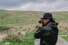 摄影师拿着一台照相机和照片 免版税库存照片