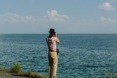 摄影师拿着一台照相机并且拍摄湖Sevan 库存照片