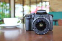 摄影师数码相机在木桌上的在咖啡馆 图库摄影