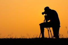 摄影师日出的射击照片剪影  免版税库存图片