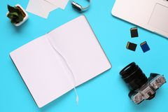 摄影师的桌面的顶视图包括在一台照相机、一台膝上型计算机、一个笔记本和一个存储卡的在蓝色书桌背景- 库存照片