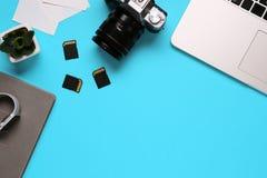 摄影师的桌面的顶视图包括在一台照相机、一台膝上型计算机、一个笔记本和一个存储卡的在蓝色书桌背景- 库存图片