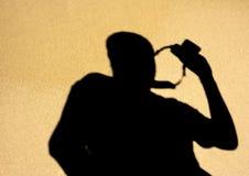 摄影师的阴影有照相机的在一湿海滩squea 免版税库存照片