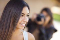 摄影师的年轻成人混合的族种女性模型姿势 库存图片