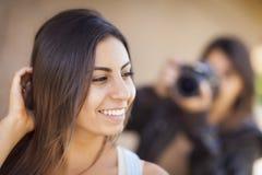 摄影师的年轻成人混合的族种女性模型姿势 免版税库存图片