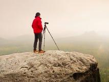 摄影师考虑在峰顶的图片在迷雾山脉 在重的薄雾掩藏的谷 库存照片