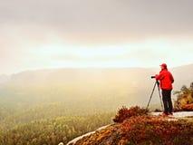 摄影师考虑在峰顶的图片在迷雾山脉 在重的薄雾掩藏的谷 免版税图库摄影
