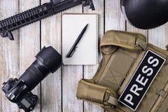 摄影记者、数字照相机、笔记本和步枪的身体装甲 免版税库存照片
