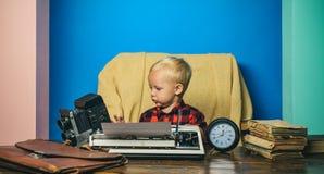 摄影记者与葡萄酒照相机和打字机一起使用 小摄影师打字在办公桌 库存照片