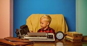 摄影记者与葡萄酒照相机和打字机一起使用 小摄影师打字在办公桌 免版税库存照片
