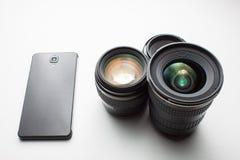 摄象机镜头和一个手机在白色 免版税库存照片