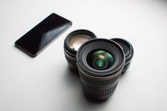 摄象机镜头和一个手机在白色 图库摄影
