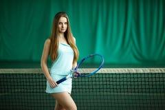 摆在一个室内网球场的性感的深色的女性网球员 库存图片