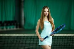摆在一个室内网球场的性感的深色的女性网球员 库存照片