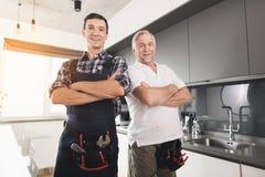 摆在一个现代厨房里的两位男性水管工 他们有一件特别制服,在他们旁边仪器的一个黑匣子 免版税库存照片