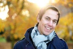 摆在一个男性的时装模特儿的微笑的面孔户外 免版税库存照片