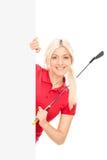 摆在一个空白的广告牌后的女性高尔夫球运动员 库存图片