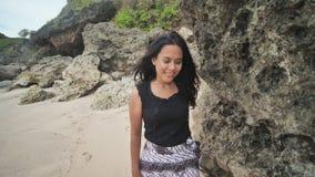 摆在一个美丽和多岩石的海滩的印度尼西亚女孩在巴厘岛 Idonezia 股票视频